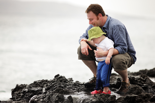 A dad and his toddler stand on the rocky shoal near the water in the summer.